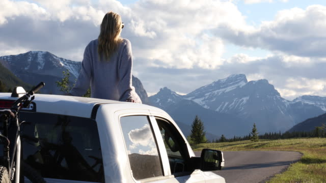 woman relaxes on top of vehicle, mountain road at sunrise - snowcapped mountain stock videos & royalty-free footage