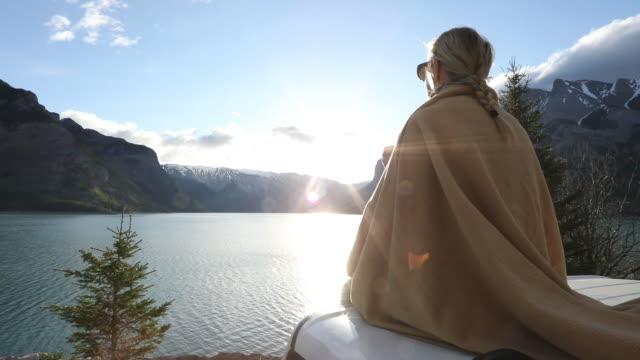 vídeos y material grabado en eventos de stock de mujer se relaja en el capó del vehículo / cabina al amanecer - manta ropa de cama