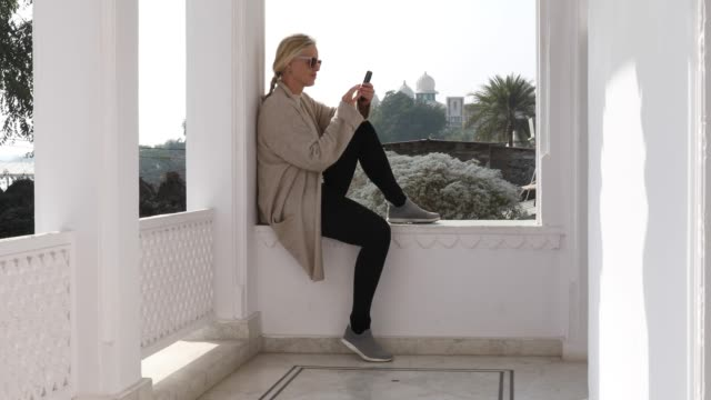 woman relaxes on window ledge, sends text - ledge stock videos & royalty-free footage