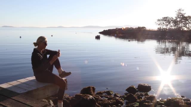 Mujer se relaja en el muelle de madera con el teléfono inteligente, sunrise