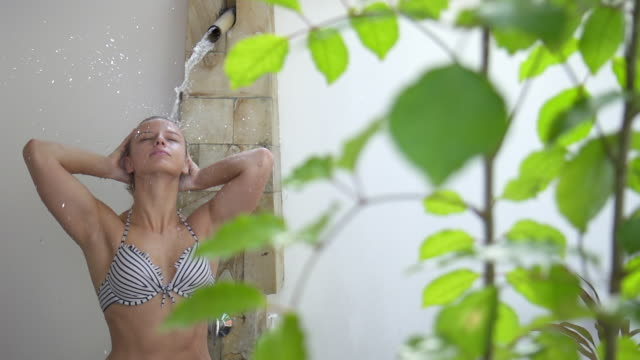 A woman relaxes under a spa shower. - Slow Motion