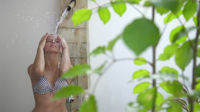 vídeos de stock, filmes e b-roll de a woman relaxes under a spa shower. - slow motion - tomar banho