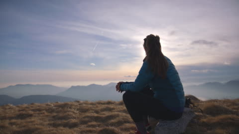woman relaxes watching sunset on top of mountain, lake below - tal stock-videos und b-roll-filmmaterial