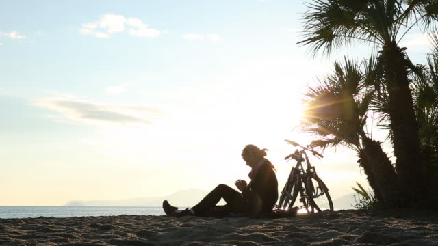 Woman relaxes with bicycle on beach, texting on smart phone