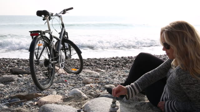woman relaxes with bike on pebble beach, stacking stones - legs crossed at ankle stock videos & royalty-free footage