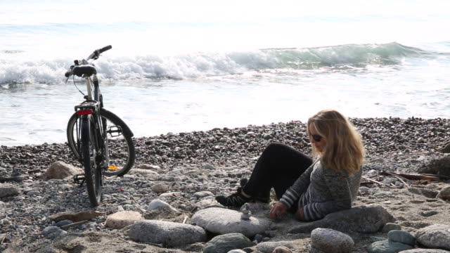 Woman relaxes with bike on pebble beach, stacking stones