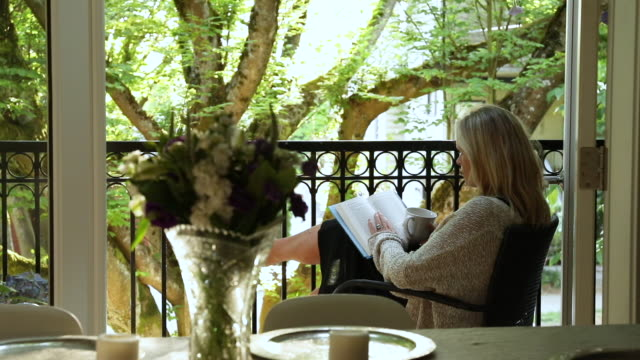 woman relaxes with book and coffee on veranda, at sunrise - book stock videos & royalty-free footage