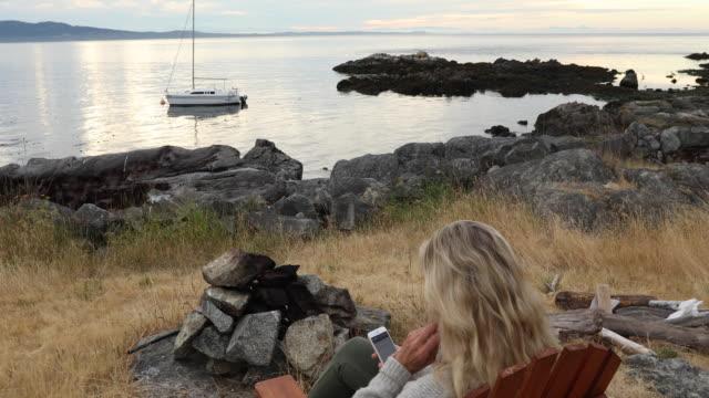 vídeos de stock, filmes e b-roll de mulher relaxa com telefone inteligente na espreguiçadeira, amanhecer - espreguiçadeira