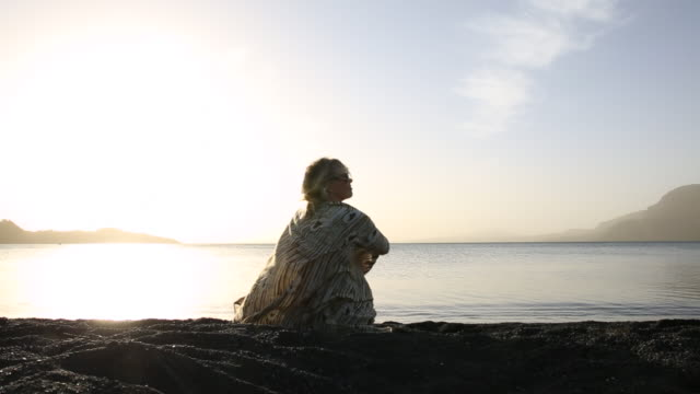 Woman relaxes/stays warm with sarong at lake edge, sunrise