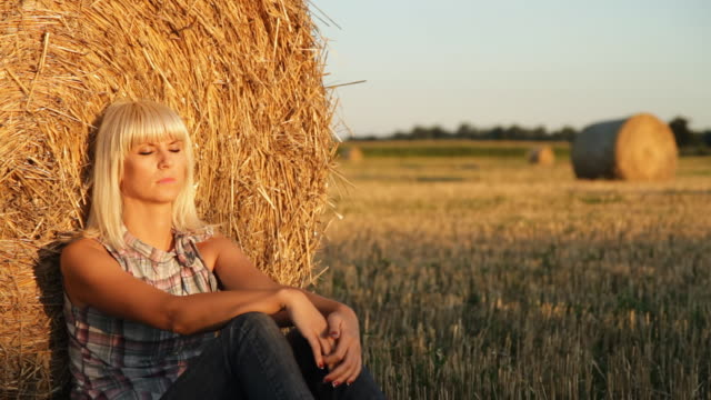 hd dolly: woman relaxing against hay bale - hay isolated stock videos & royalty-free footage