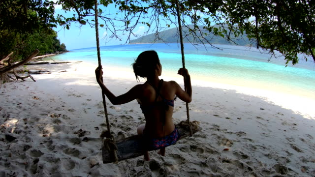 woman relaxing and enjoy in beach hammock at south of thailand - cappello video stock e b–roll