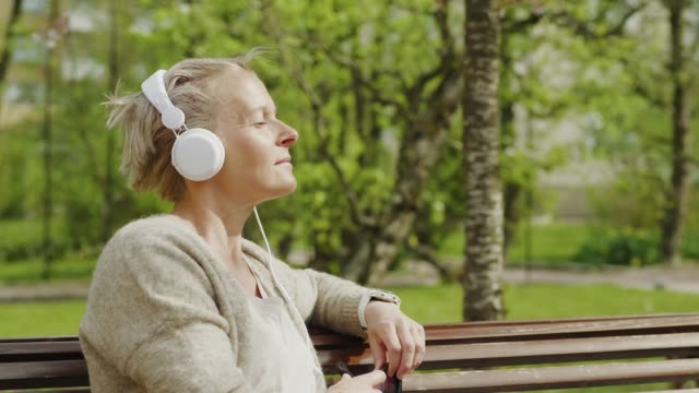 woman relaxing and listening to music in the park - sitting video stock e b–roll