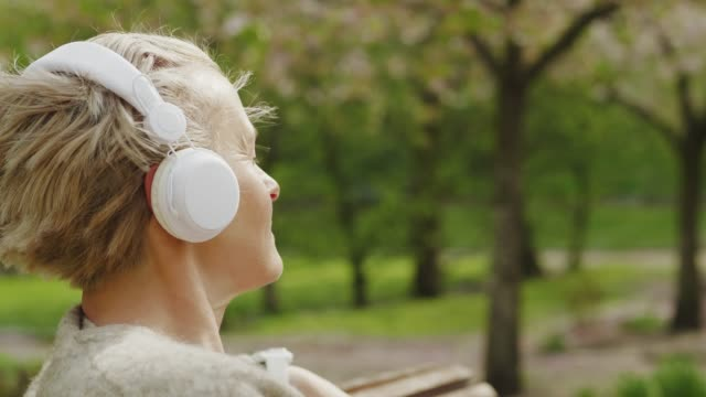 woman relaxing and listening to music in the park - mature adult stock videos & royalty-free footage