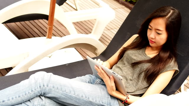 Woman relaxing and using a digital tablet