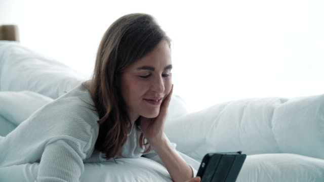 Woman relaxing and using digital tablet on bed