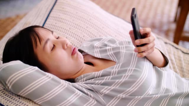 woman relaxing and using smart phone - bean bag stock videos & royalty-free footage