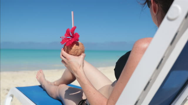 vídeos de stock, filmes e b-roll de mulher, relaxante na praia na cadeira com bebida, cuba - toalha de praia