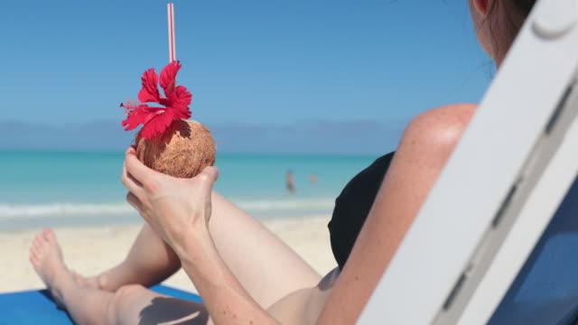 frau entspannung am strand auf stuhl mit getränk, kuba - eibisch tropische blume stock-videos und b-roll-filmmaterial