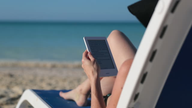 Woman Relaxing at Beach with Electronic Book Reader