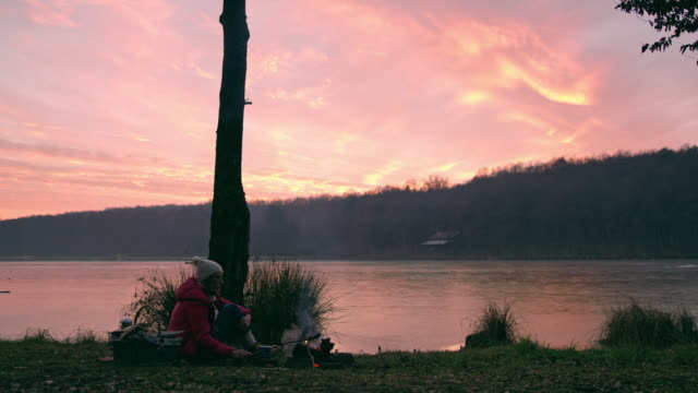 ms woman relaxing at campfire by tranquil autumn sunset lakeside,prekmurje,slovenia - prekmurje stock videos & royalty-free footage