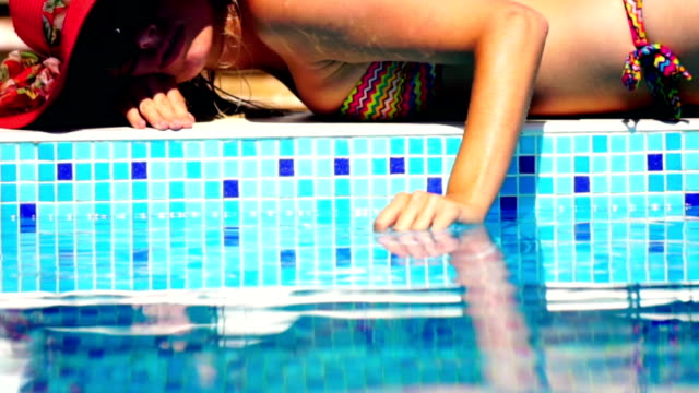 Woman relaxing at poolside.