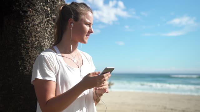 Frau Entspannung am Strand nach ausgeführt und mit Smartphone
