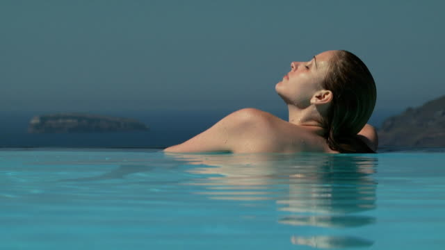 A woman relaxing at the edge of an infinity pool