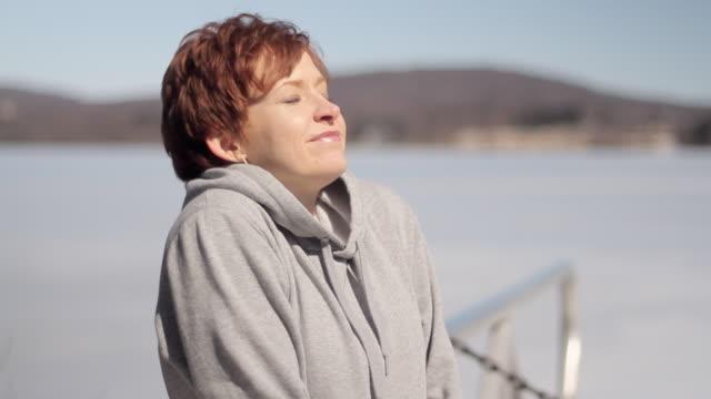 vidéos et rushes de cu woman relaxing by frozen lake / glen gardner, new jersey, usa - cheveux bruns