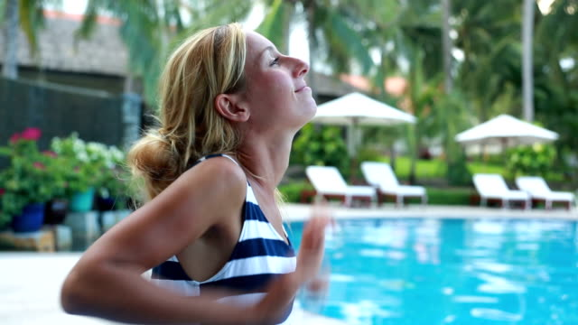 woman relaxing by the pool, arms outstretched - human limb stock videos & royalty-free footage