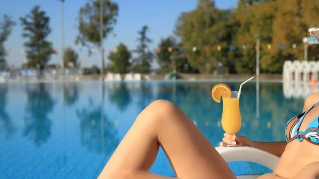 vídeos y material grabado en eventos de stock de dolly hd: mujer descansando junto a la piscina - tumbona