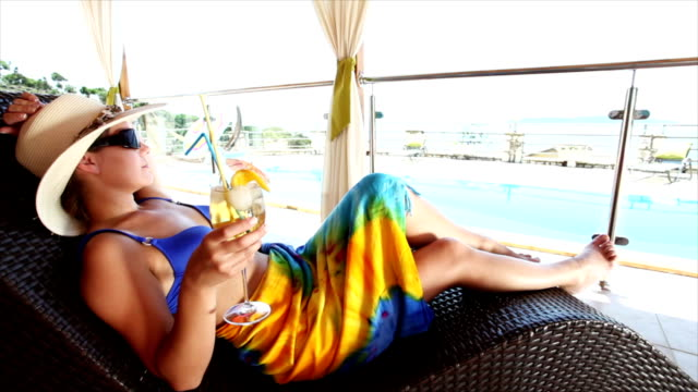 hd crane: woman relaxing by the swimming pool - tropical drink stock videos and b-roll footage