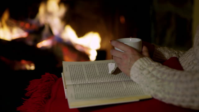 4k woman relaxing, drinking tea and reading book by cozy fireplace, real time - cup stock videos & royalty-free footage
