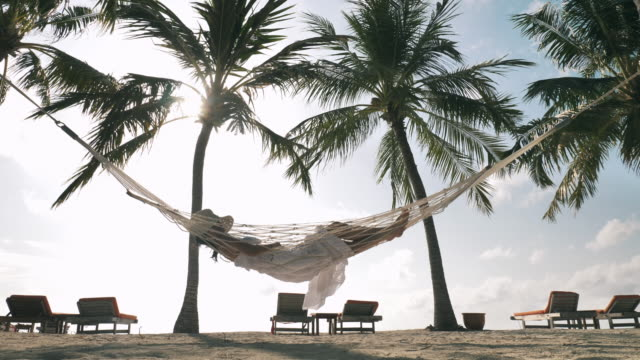 kvinna avkopplande hängmatta på stranden - hängmatta sol bildbanksvideor och videomaterial från bakom kulisserna