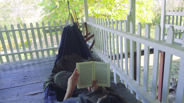 vidéos et rushes de woman relaxing in a hammock reading a book. she is at the porche of the cabin surrounded by the white fence. retreat - brief - back lit