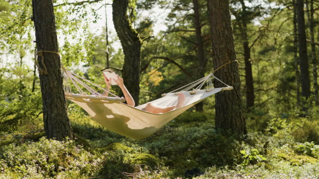woman relaxing in a hammock with a good book - hammock stock videos & royalty-free footage