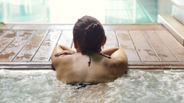 vídeos de stock e filmes b-roll de woman relaxing in a hot tub pool during weekend days of relax and spa in a luxury place during travel vacations. - só uma mulher jovem