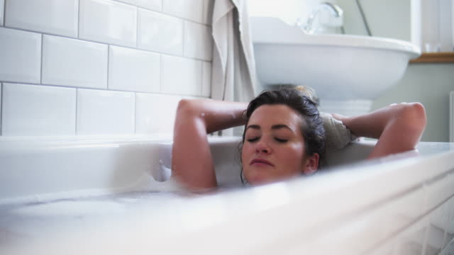woman relaxing in bath tube. - vasca da bagno video stock e b–roll