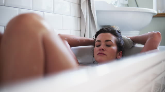 stockvideo's en b-roll-footage met woman relaxing in bathtub. - domestic bathroom