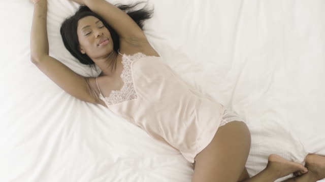 vidéos et rushes de woman relaxing in bed - underwear
