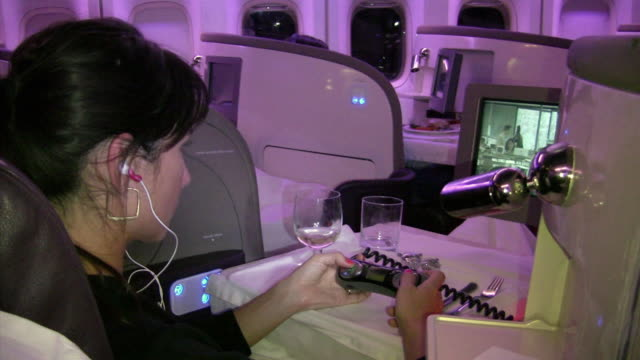 vidéos et rushes de cu, woman relaxing in first class of plane, drinking wine and watching movie - première classe