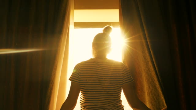 woman relaxing in front of the window. - sunrise dawn stock videos & royalty-free footage
