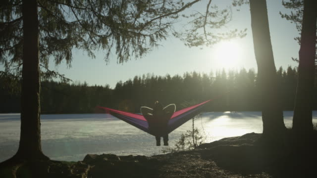 kvinna koppla av i hängmatta vid sjön - bekväm bildbanksvideor och videomaterial från bakom kulisserna