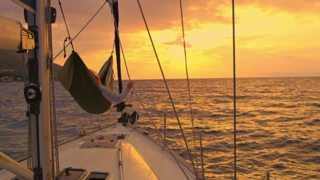 4 k frau zum entspannen in der hängematte auf windigen segelboot auf ruhigen sonnenuntergang ozean, real-time - gemütlich stock-videos und b-roll-filmmaterial