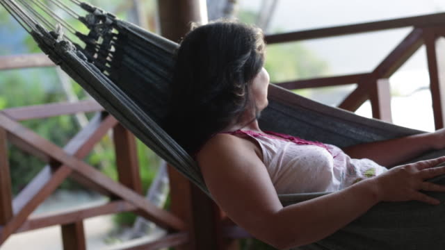vídeos de stock, filmes e b-roll de woman relaxing in hammock raises her head to look at view. - rede de dormir