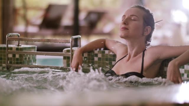 stockvideo's en b-roll-footage met vrouw ontspannen in het bubbelbad in spa - binnenbad