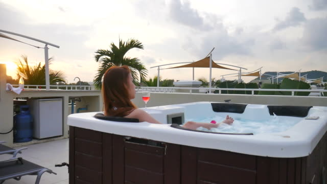 Woman relaxing in hot tub outdoors with wine at sunset