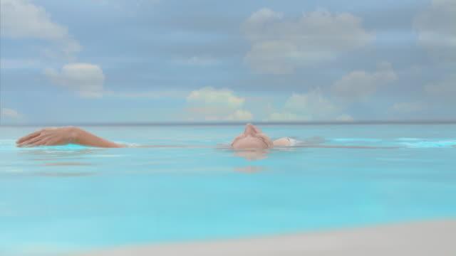 vídeos y material grabado en eventos de stock de slo mo ms mujer relajarse en piscina infinita - flotar sobre agua