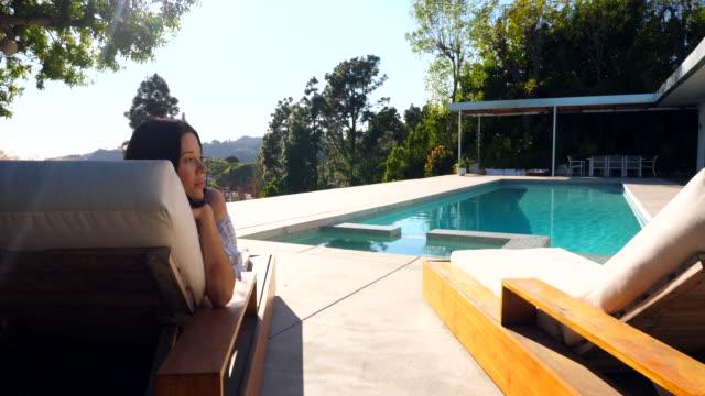 vídeos de stock, filmes e b-roll de ws woman relaxing in lounge chair by pool - ao lado de piscina