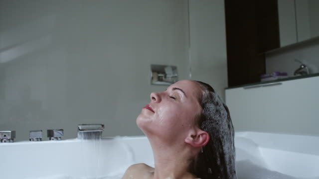 woman relaxing in modern bathtub - vasca da bagno video stock e b–roll