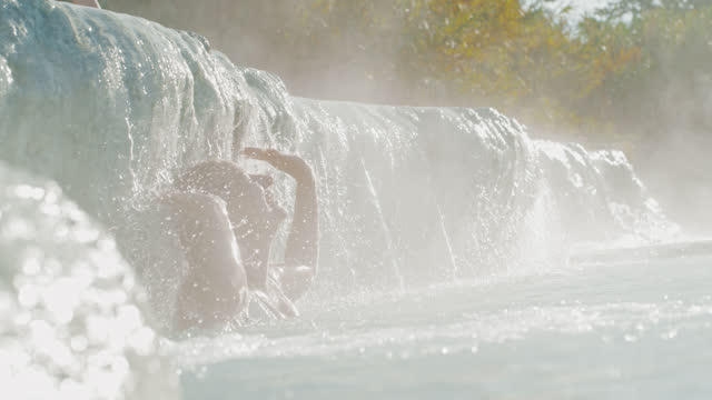 super slo mo woman relaxing in natural pool at the saturnia hot springs in tuscany - hot tub stock videos & royalty-free footage
